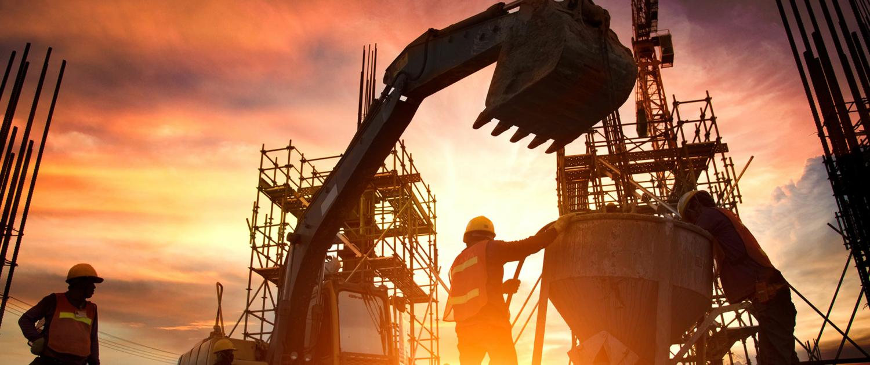 Baustelle mit Bagger und zwei Bauarbeitern im Sonnenuntergang