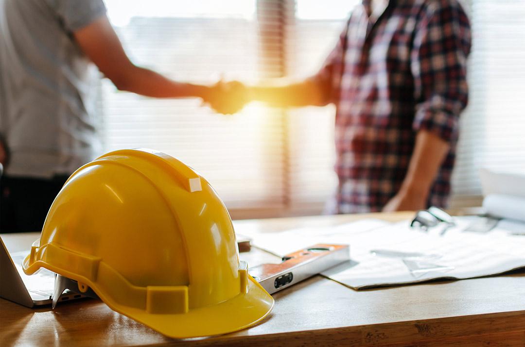 Büro auf Baustelle - Handschlag von Architekten - mit Bauhelm im Vordergrund